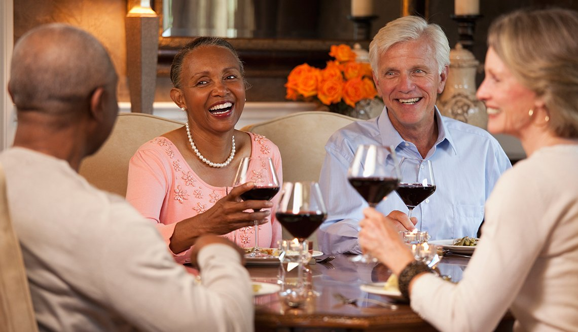 Smiling-couples-toasting-wine-glasses-at-dining-room-table