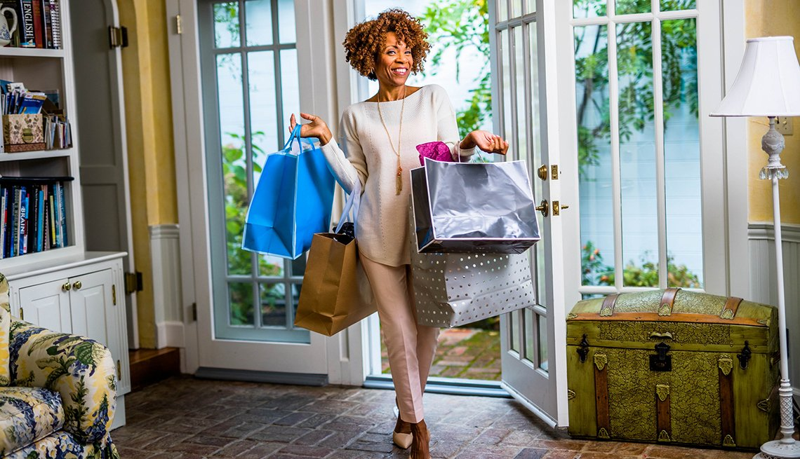 Smiling woman walking into home with multiple shopping bags