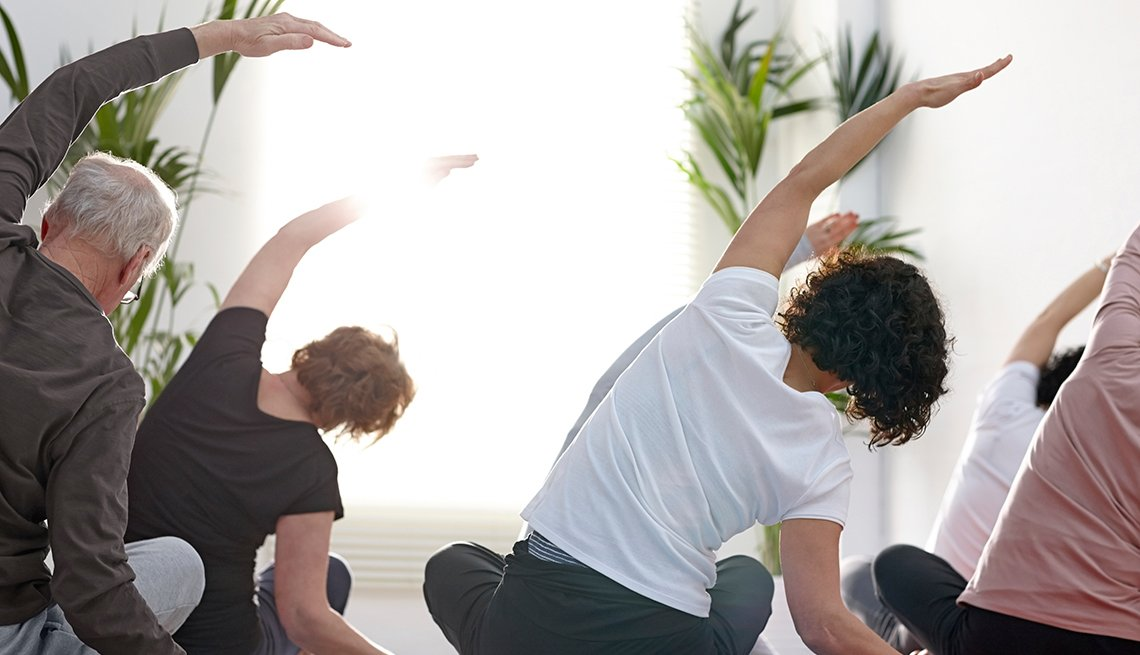 Group of people in the gym doing stretching exercise in yoga class
