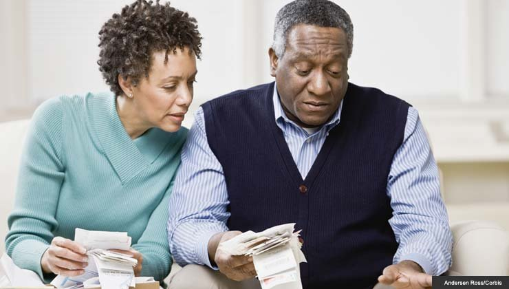 African couple adding up receipts