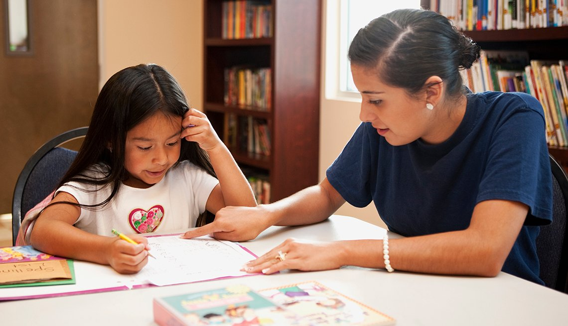 Woman and Child in Library, Reading Work, AARP Foundation's Experience Corps
