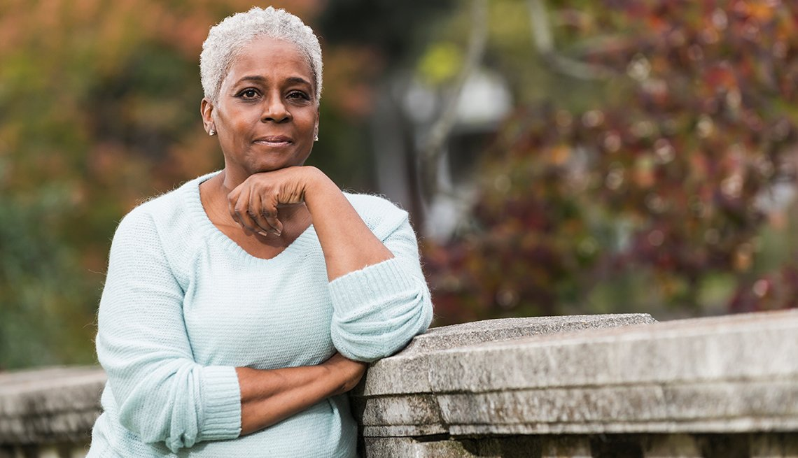 Mature African-American woman, outdoors, stone railing, AARP Foundation, Find Help, Local Assistance Directory