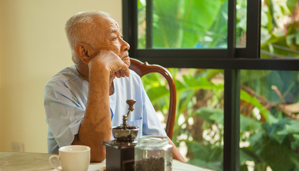 A mature Asian man, looking out a window, sitting at a table, AARP Foundation Litigation, Legal Advocacy