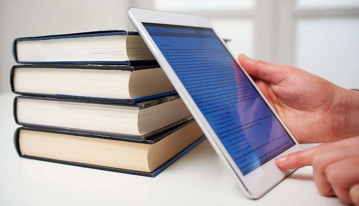 Digital tablet with pile of printed paper books, Finances 50 plus, AARP Foundation