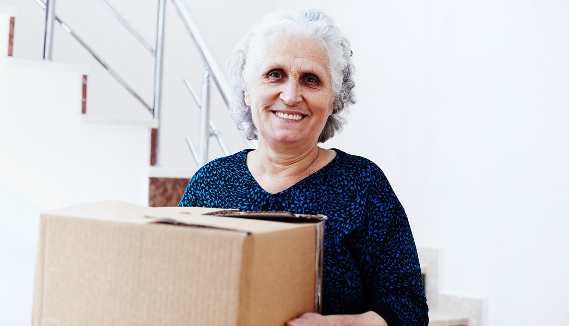 mature woman holding box inside house, AARP Foundation, Our Work, Housing