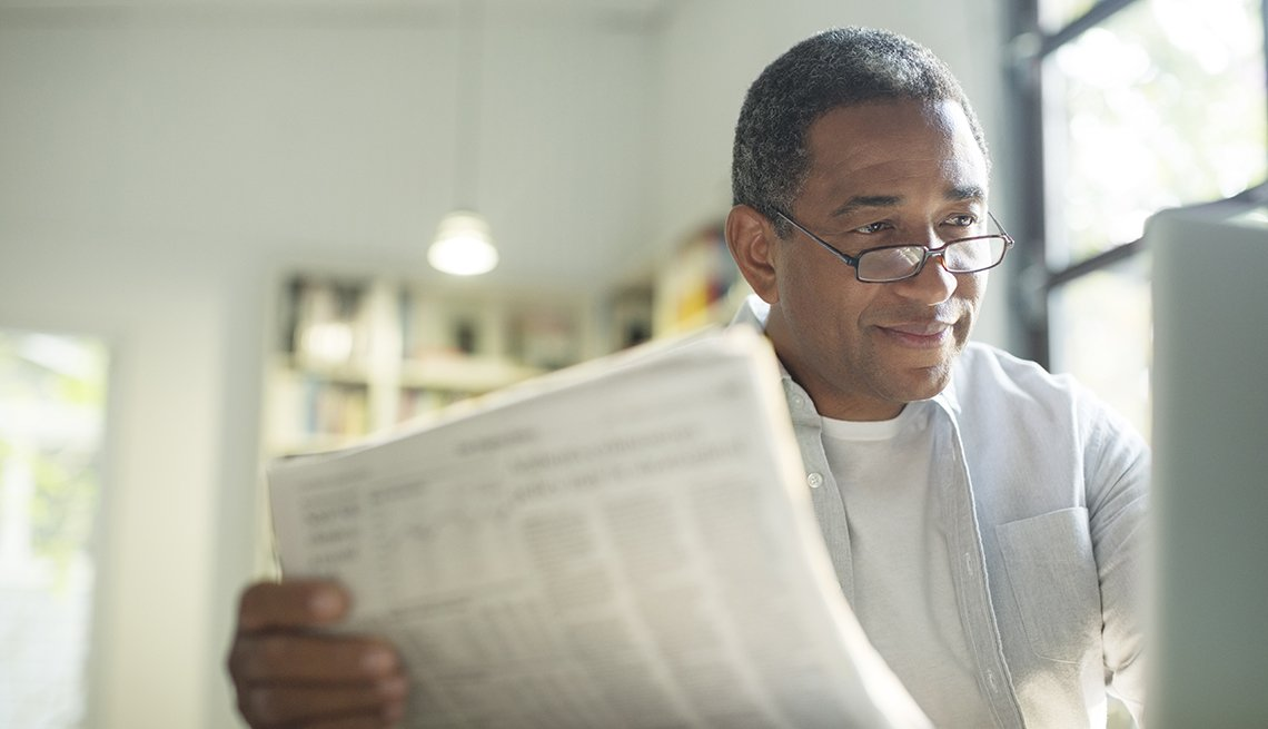 African-American man, reviewing paperwork, computer, Housing Solutions Center, AARP Foundation