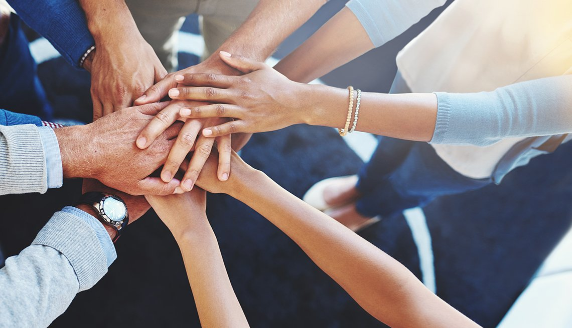 Multi-ethnic group of business people, Huddle, Hands together, Volunteer, AARP Foundation, ElderWatch program