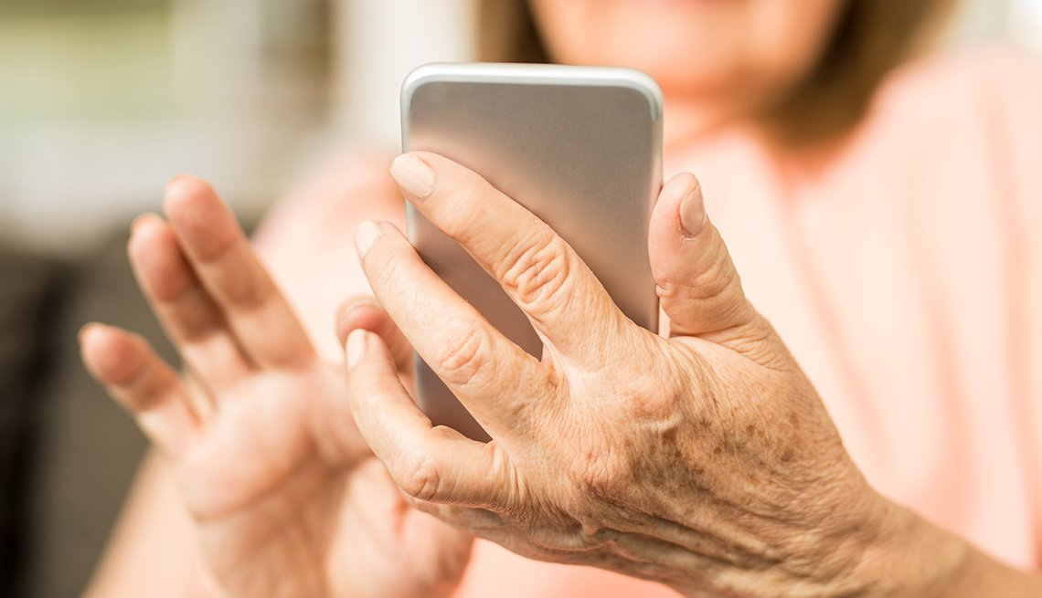 Mature woman using smartphone, beware of phone scams, AARP Foundation, Elderwatch