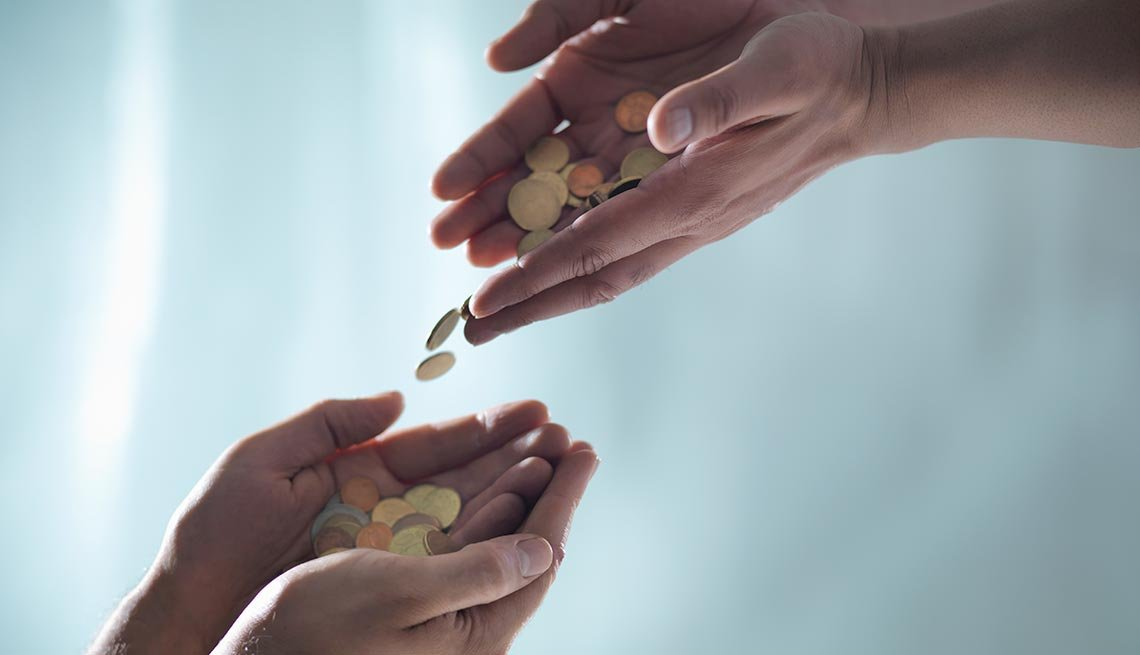 Hands exchanging coins - Donate - AARP Everywhere