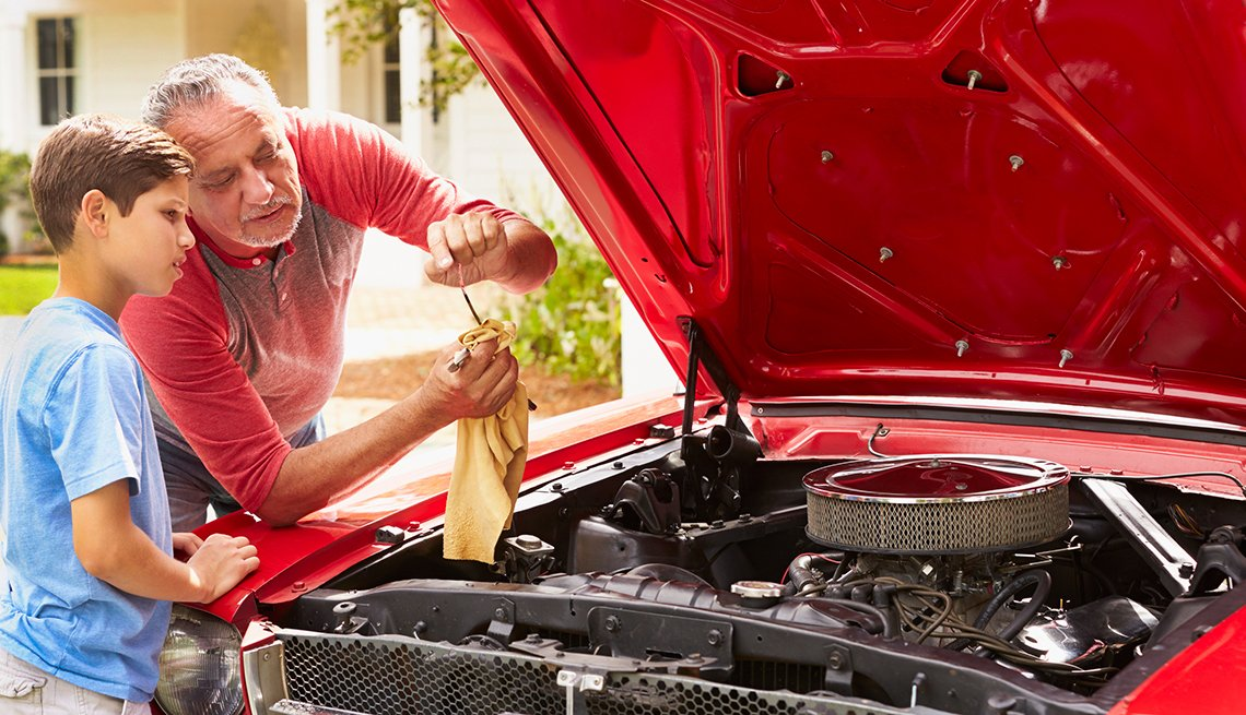 Dad showing son how to check car oil