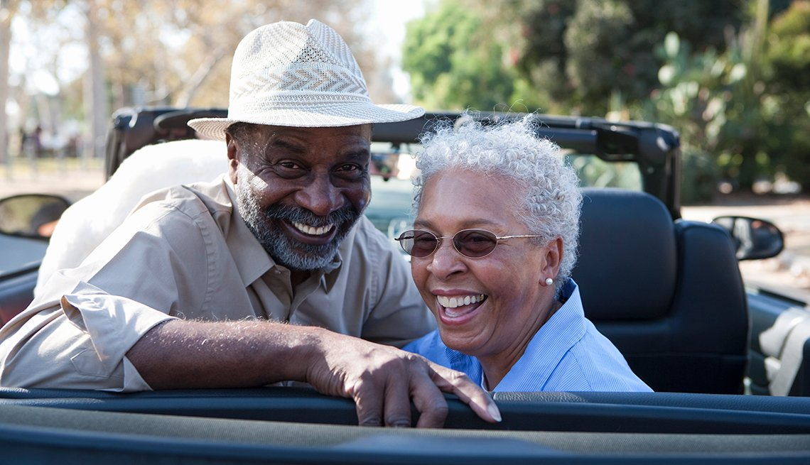 Happy mature African-American couple, back of car, convertible, AARP Auto Buying Program