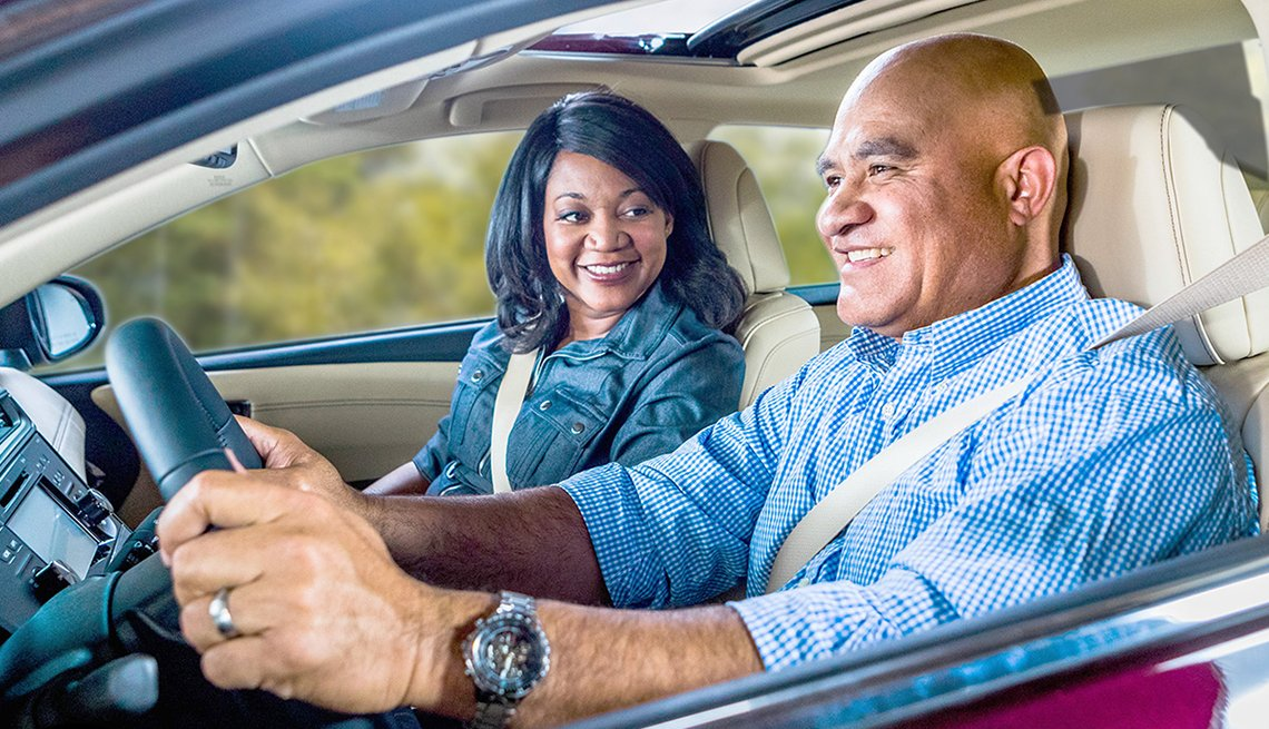 An African-American man drives his car with his wife in passenger seat.