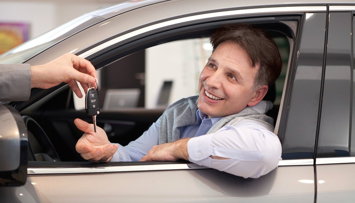 Man handing car keys to man inside car.