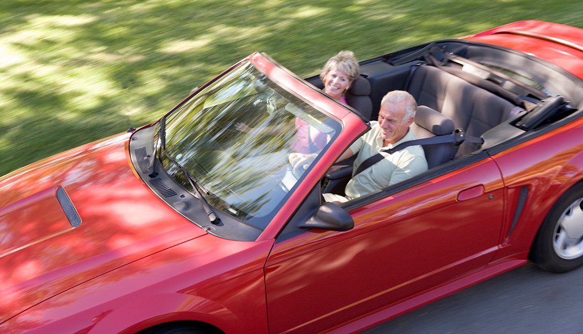 Couple in convertible car smiling, Auto Insurance