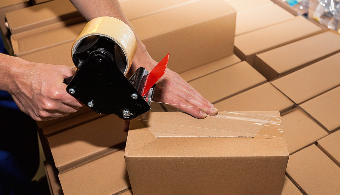 Worker using adhesive tape to close the boxes, UPS