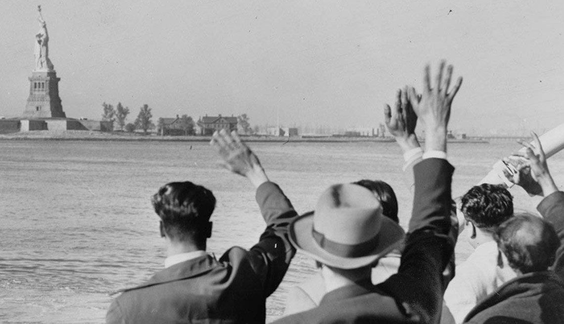 Black and white image of men waving from boat at the state of liberty in New York.