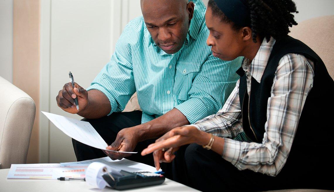 Pareja afroamericana viendo unos documentos y haciendo cuentas porque hay que tener cuidado con las estafas financieras