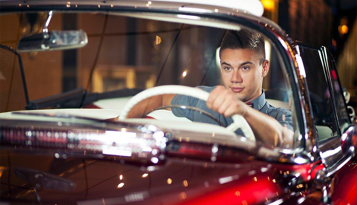 Teen boy driving classic convertible