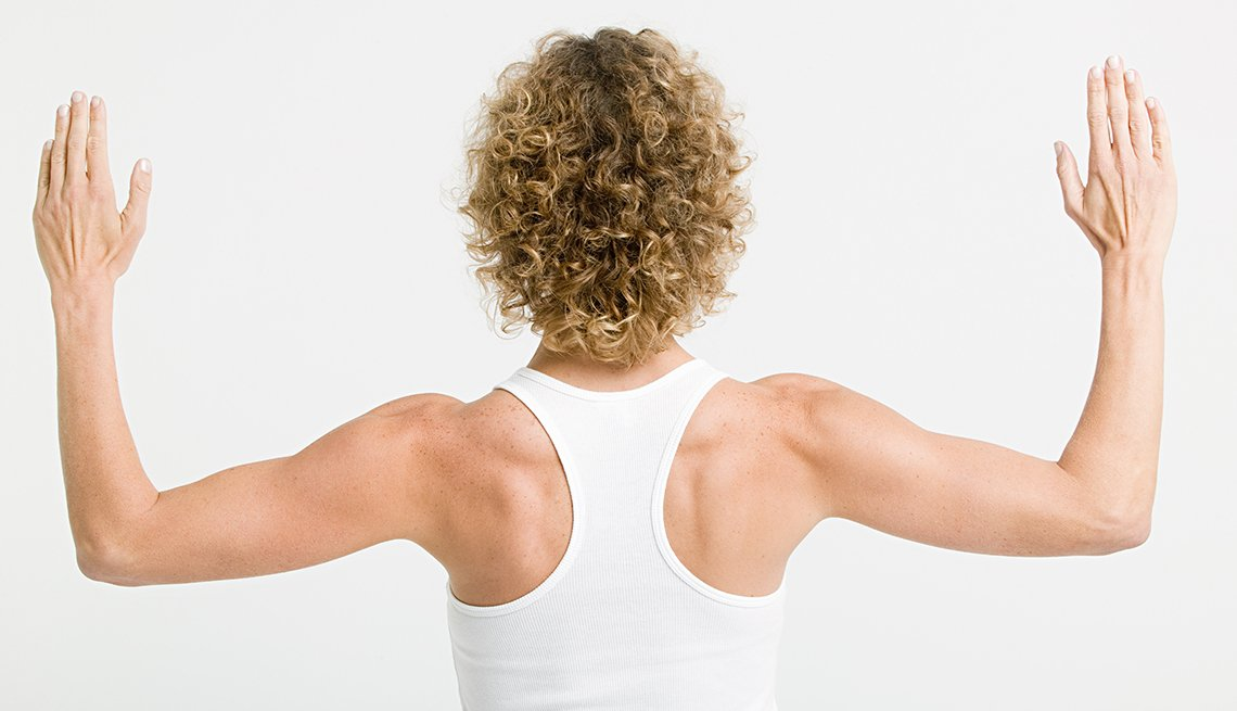 A flexible woman stretching her arms showing muscles