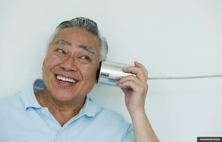 Smiling man with tin can phone, AARP Public Policies Book Feedback (Asiaselects/Alamy)