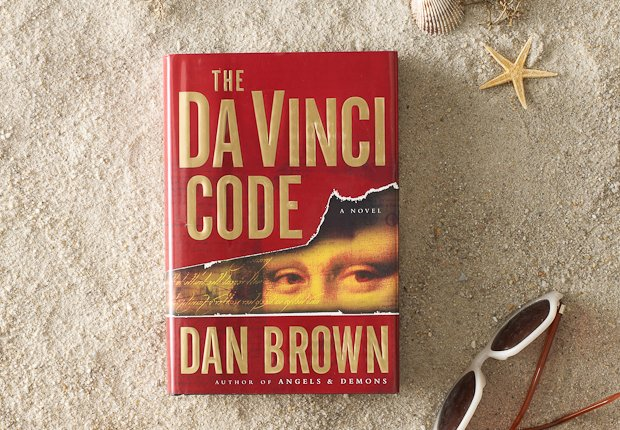 Beach scene with classic book THE DA VINCI CODE perched up in the sand, Power of 50 Summer Books