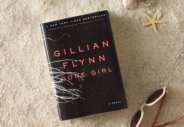 Beach scene with classic book GONE GIRL perched up in the sand, Power of 50 Summer Books