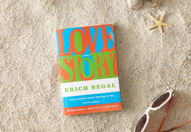 Beach scene with classic book LOVE STRY perched up in the sand, Power of 50 Summer Books