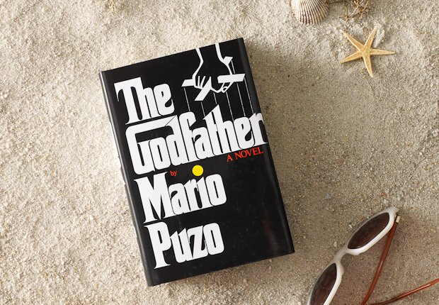Beach scene with classic book THE GODFATHER perched up in the sand, Power of 50 Summer Books