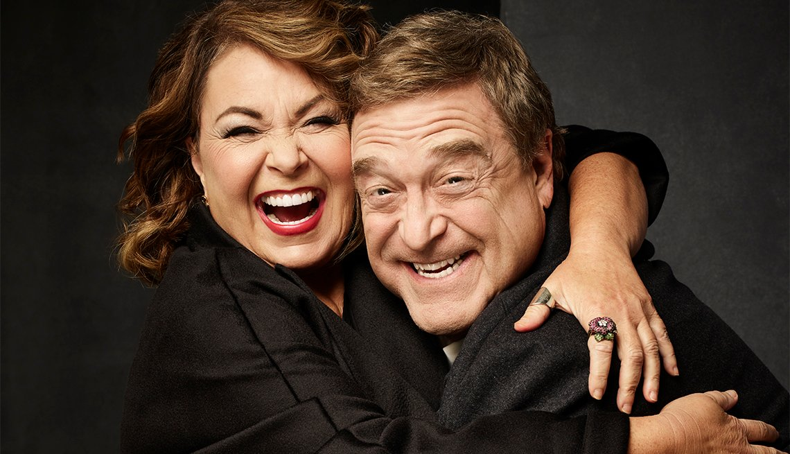Roseanne Barr and John Goodman hugging and laughing
