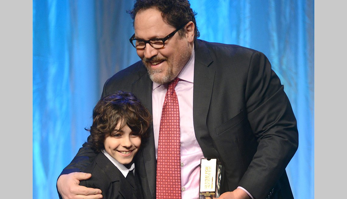 Emjay Anthony, left, Jon Favreau are seen after Favreau accepted an award for Best Comedy for