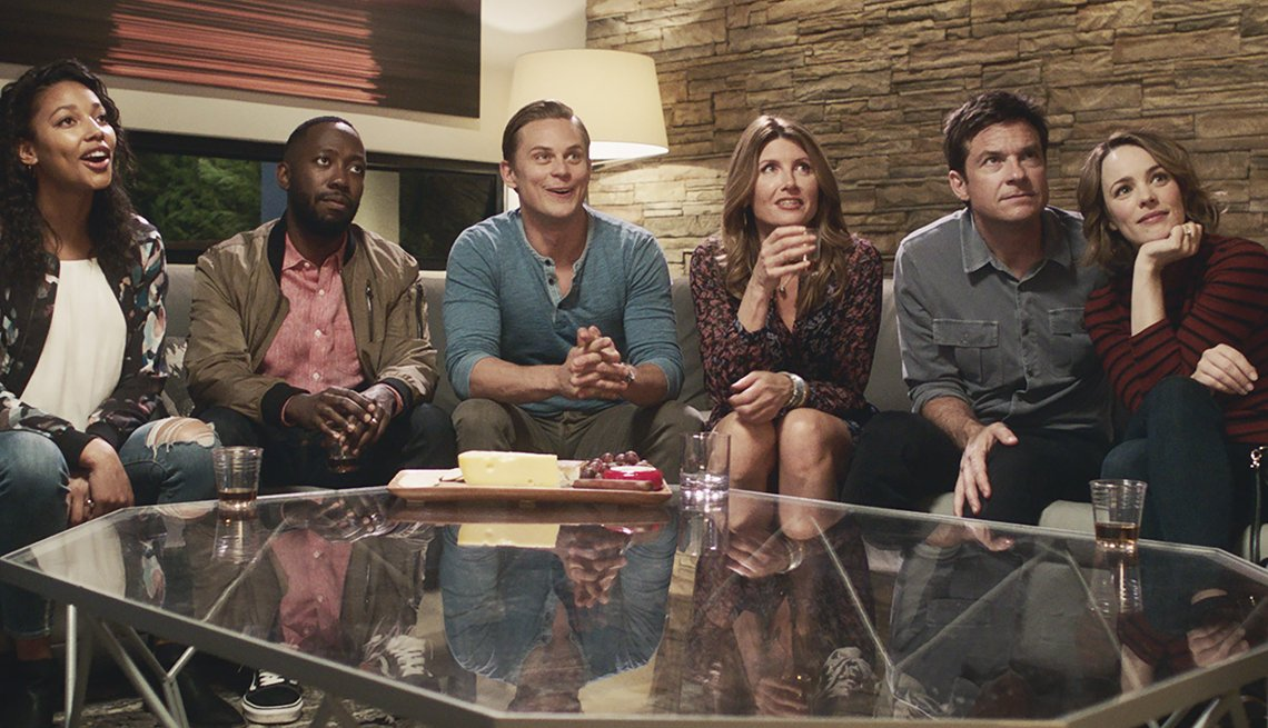 still from the movie 'Game Night', featuring six people sitting in a living room