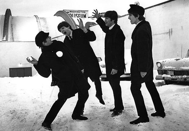 The Beatles soon after their arrival in Washington, USA, playing in the snow outside the Coliseum where they were scheduled to perform before a sell-out audience.