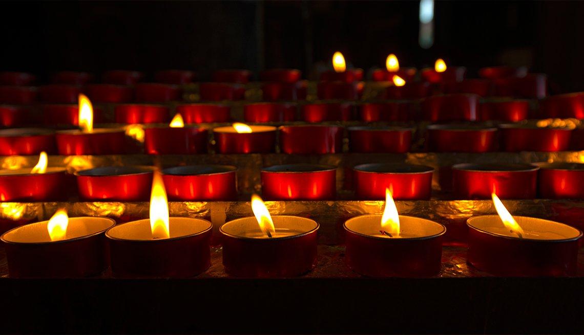 Votive candles in dark church