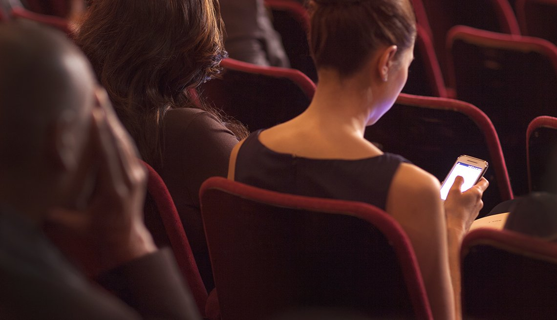 woman using her phone in a theater