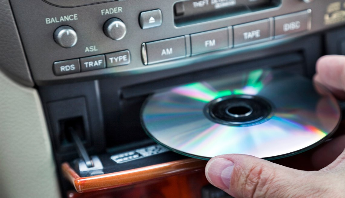 Man inserting CD in car player
