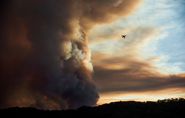 An aircraft circles a smoke column as the Loma fire burns