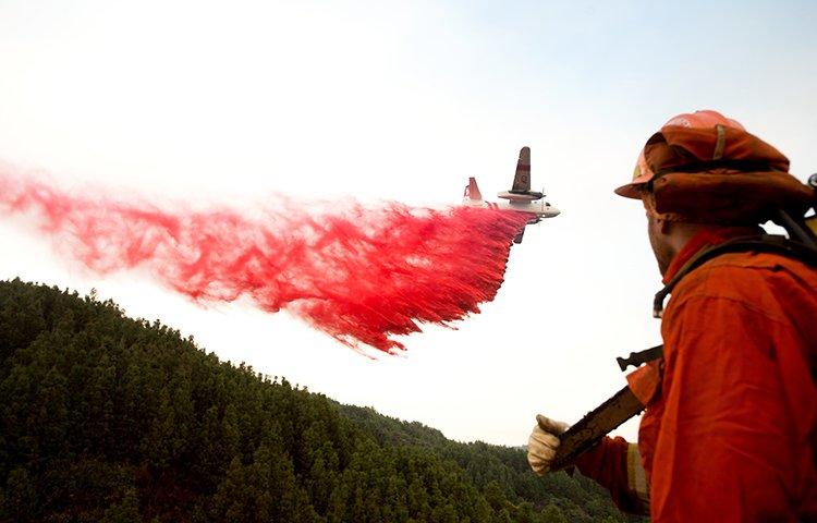 an air tanker drops retardant while battling a wildfire near Morgan Hill,
