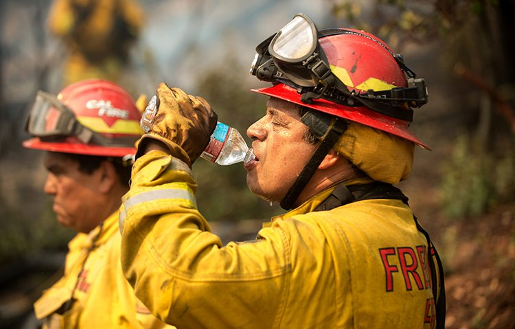 Capt. Dan Cardenas, 61, a firefighter with the Fremont Fire Department, drinks water while battling the Loma wildfire