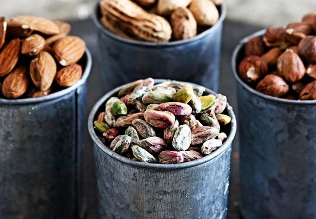 Selection of nuts on table in pots, calorie dense foods