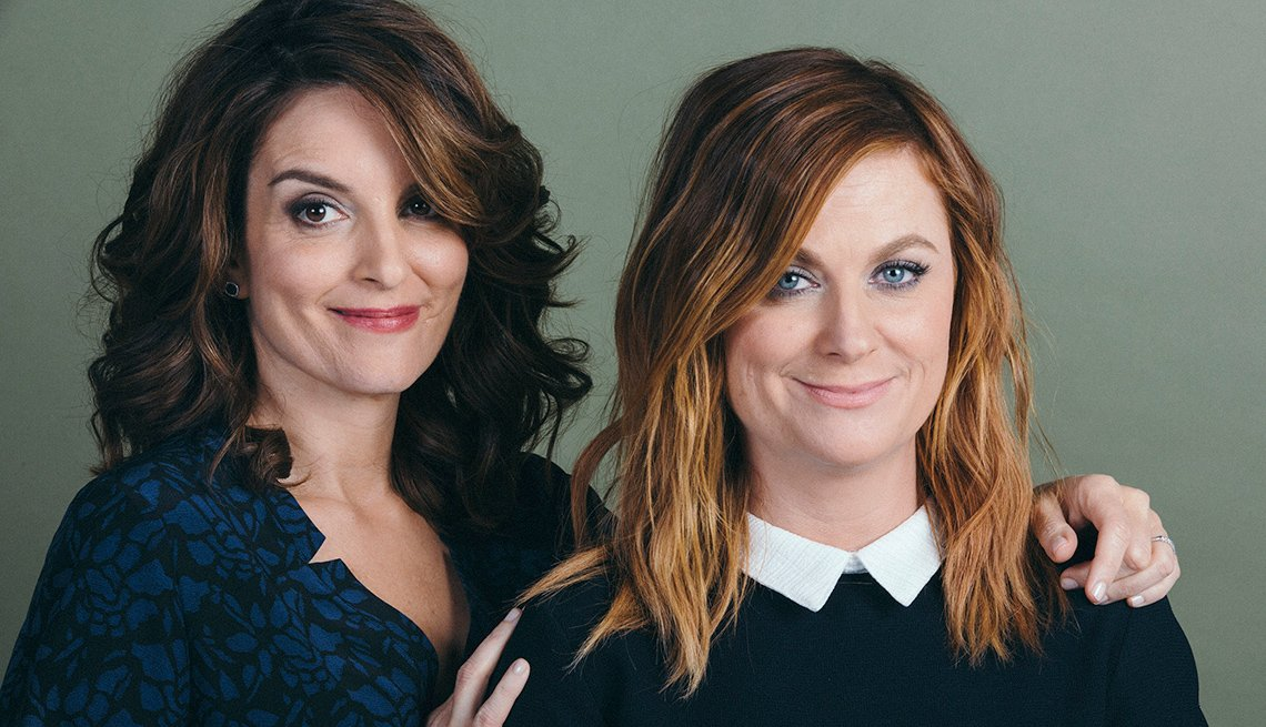 Friends Tina Fey and Amy Poehler pose for a portrait smiling