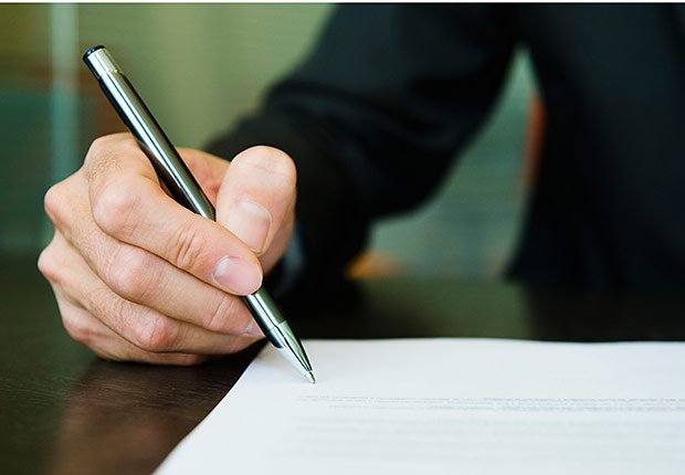 Man signing paperwork, How to Get the Right Hearing Aid: 10 Tips
