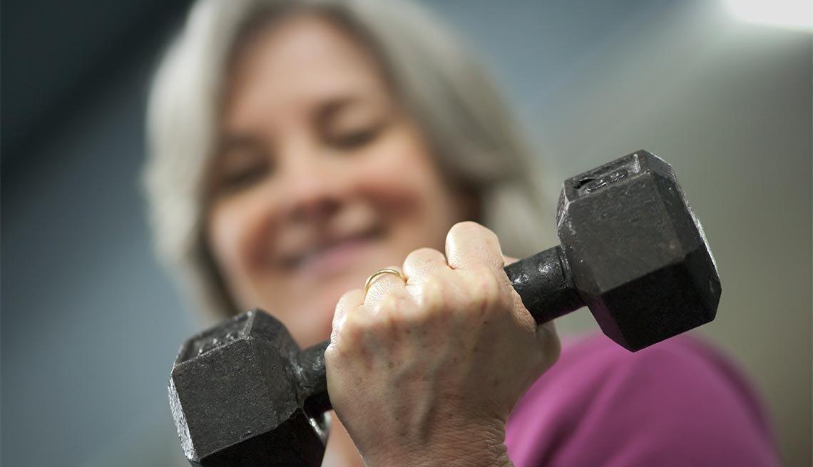 Mujer levanta una mancuerna, una forma de fortalecer tus huesos