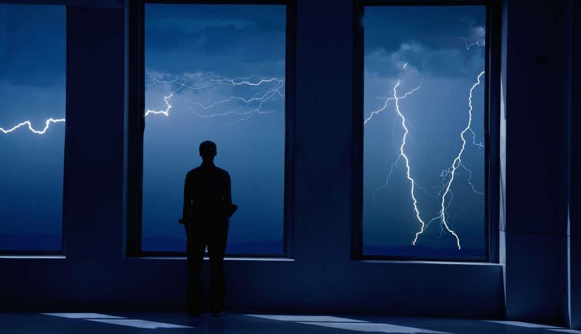 Hombre observando relámpagos caer en la noche