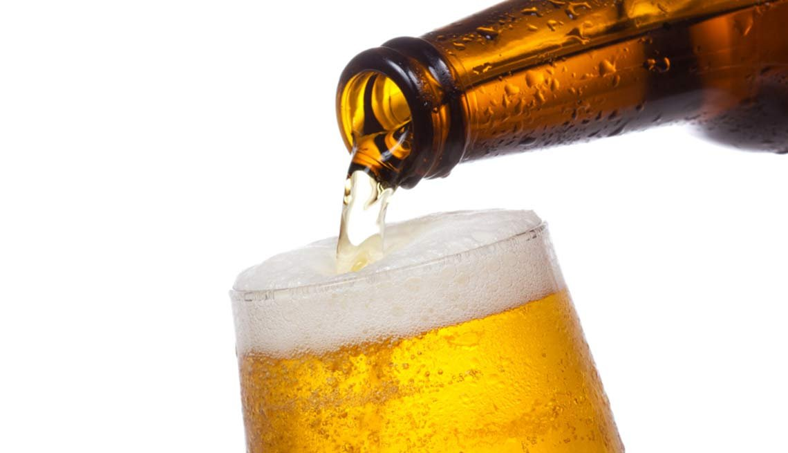 Beer pouring into glass, beer-better-at-reducing-a-womans-chance-of-arthritis
