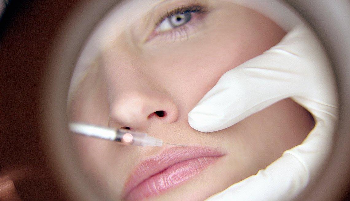 Médico inyectando los labios de una mujer - Estética