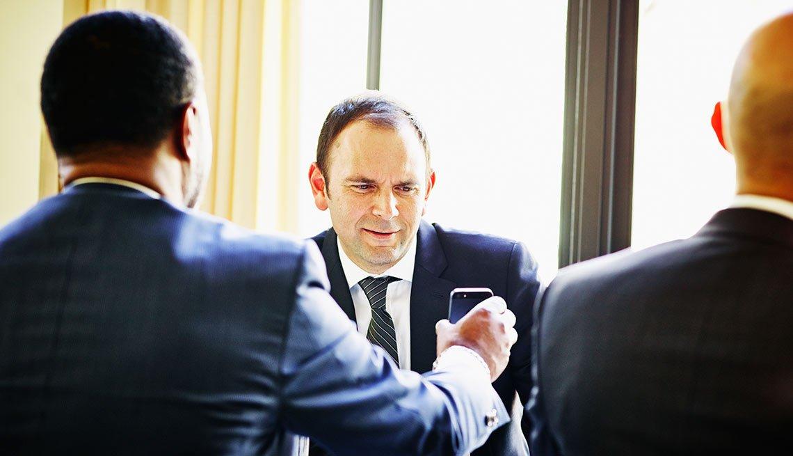Hombres mirando a un celular en gesto de asombro
