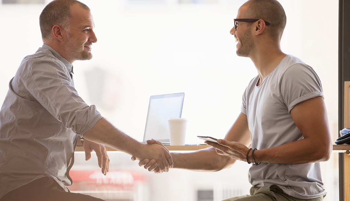 Men shaking hands seated at a table, Workplace hearing loss coping strategies