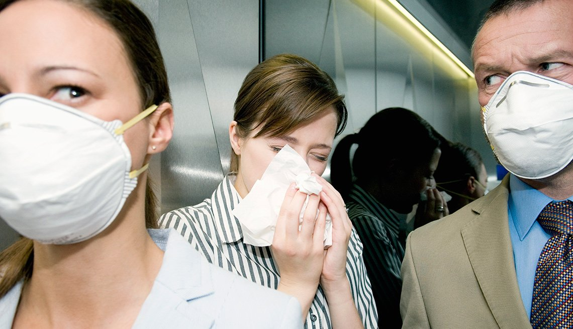 people wearing flu masks in an elevator with a sneezing woman