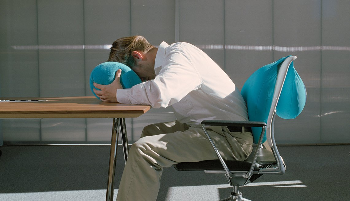 man sitting at desk with face in a pillow