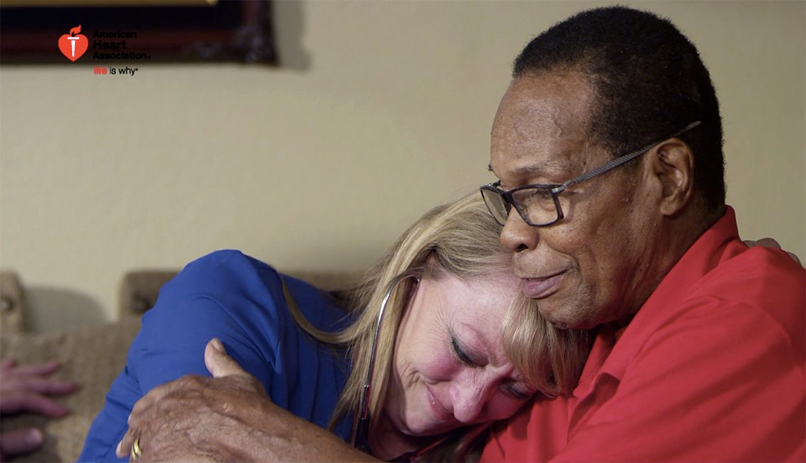 Older man hugs older woman while sitting on couch